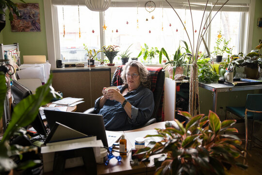 Senior woman on break, looking at laptop in home office
