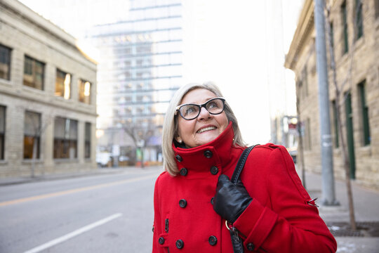 Happy senior woman in red winter coat looking up at city building