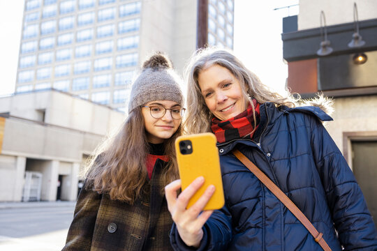 Mother and teenage daughter taking selfie on city street corner