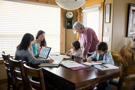 Family assisting children with homework at table
