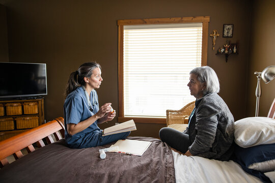 Nurse consulting with senior woman on bed