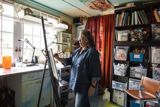 Portrait of senior woman painting on canvas