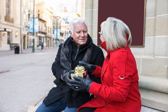 Senior man giving Christmas gift to wife on urban street corner