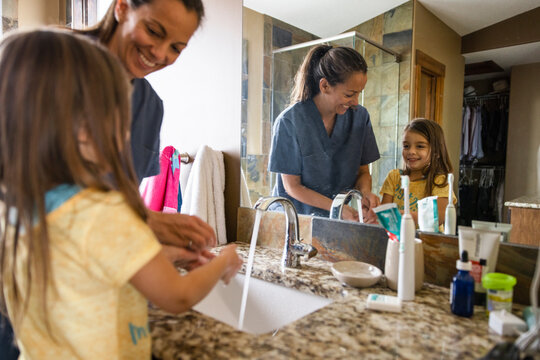 Mother helping daughter wash hands in bathroom