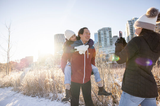 Happy father piggybacking daughter in sunny snowy winter city park