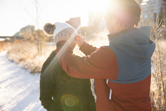 Father adjusting stocking cap on teen daughter in sunny snowy park