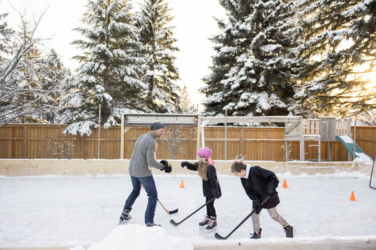 Father and kids playing ice hockey on snowy backyard ice rink
