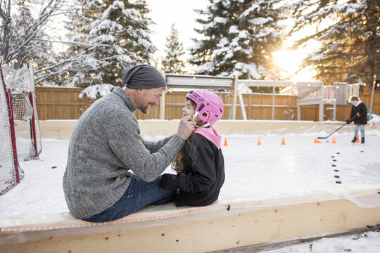 Happy father helping daughter with helmet at backyard ice hockey rink