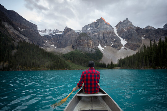 Rear view of man canoeing on lake with mountains