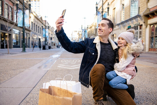 Father and daughter with shopping bags taking selfie in winter city