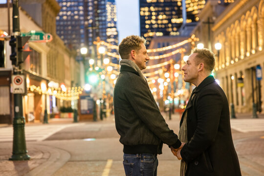 Gay male couple holding hands talking on city street at night