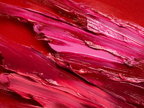 Smudged lipsticks over red background