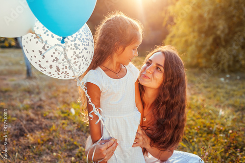 Mother's day. Little girl walking with mother and holding baloons. Family having fun in summer park. Woman hugging kid