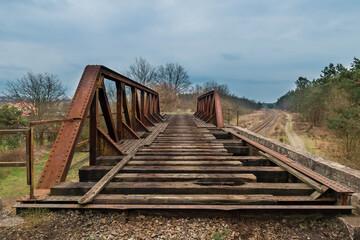 Stary, nieużytkowany most kolejowy.