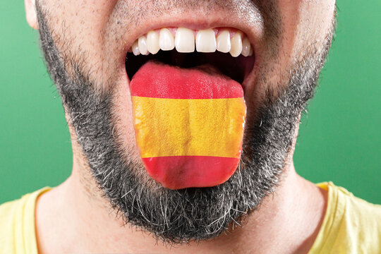 Native speaker. The protruding tongue of a bearded man is close-up, in the colors of the Spanish flag. The concept of learning foreign languages