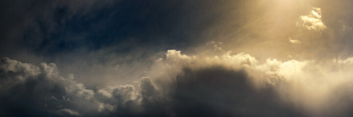 Fototapeta panoramic view of dramatic sky with cumulus clouds and bright sunlight
