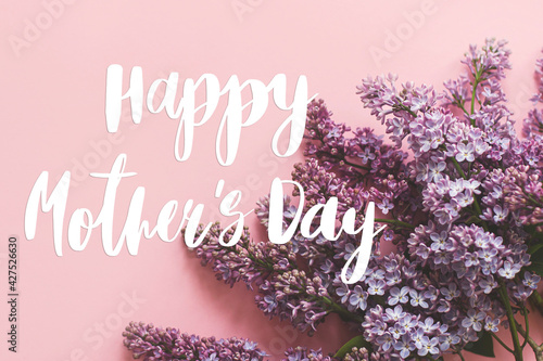 Happy mother's day. Happy mother's day text and lilac flowers on pink paper. Stylish floral greeting card. Handwritten lettering on purple lilac branch on pink. Mothers day