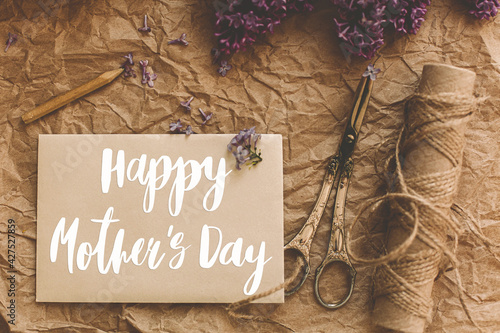 Happy mother's day. Happy mother's day text on card and lilac flowers, pencil, vintage scissors, twine on rustic background. Stylish floral greeting card. Handwritten lettering. Mothers day