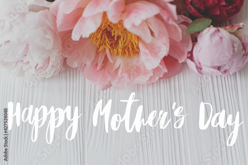 Happy mother's day greeting card. Happy mother's day text and  peony floral border on white wood. Stylish floral greetings. Handwritten lettering. Mothers day