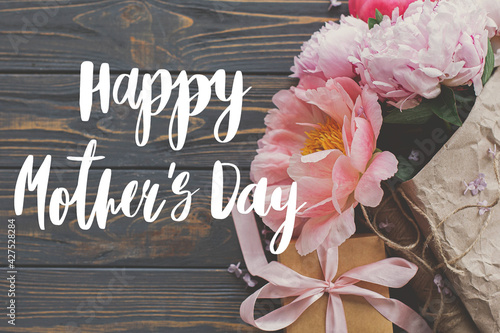 Happy mother's day. Happy mother's day text and peony bouquet in paper, gift box on rustic dark wood flat lay. Stylish floral greeting card. Handwritten lettering. Mothers day