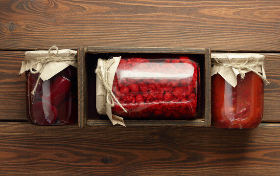 Raspberry compote in plastic free sustainable glass jar in wooden box on rustic background, closeup, copy space, canned produce, saving leftovers, food storage concept