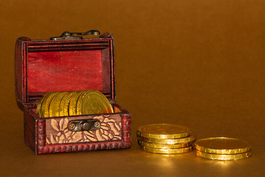 Chest with chocolate coins on brown background
