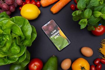 Telefon z tekstem low FODMAP diet na ekranie, otoczony warzywami i owocami, zdrowa dieta i odżywianie