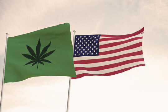 Interesting Flags of the United States of America and that of the legalization of marijuana waving with the bright sky in the background.