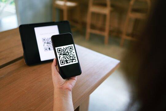 Qr code payment. Woman scanning QR code online shopping cashless technology concept.