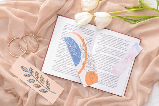 Book with bookmarks and flowers on color background