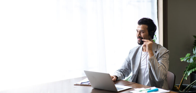Attractive business man in suits and headsets smiling while working on desktop computer at modern office desk . Customer service assistant working in office. VOIP Helpdesk headset