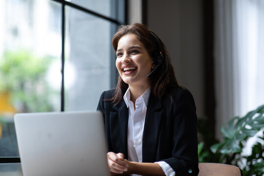 Attractive business woman Asian in suits and headsets are smiling while working with computer at office. Customer service assistant working in office. VOIP Helpdesk headset