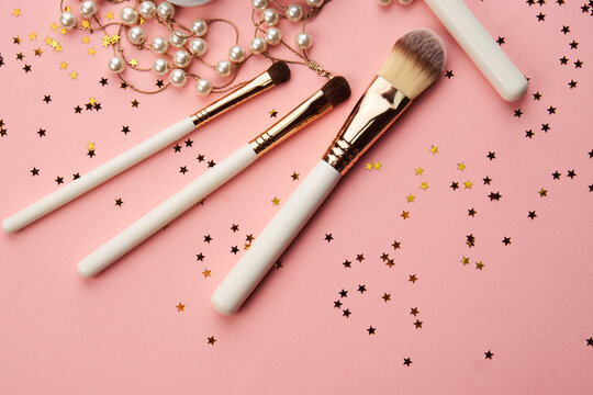 Female makeup decoration accessories on the table pink background top view