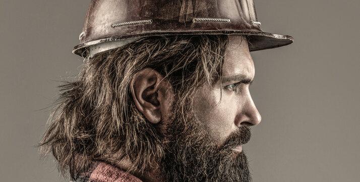 Man builders, industry. Builder in hard hat, foreman or repairman in the helmet. Building, industry, technology - builder concept. Bearded man worker with beard in building helmet or hard hat