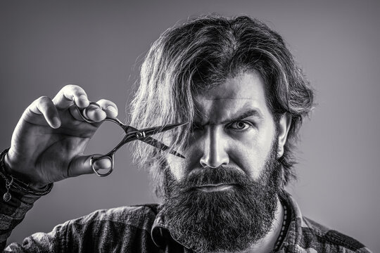 Male in barbershop, haircut, shaving. Bearded man isolated on gray background. Barber scissors, barber shop. Barber scissors. Vintage barbershop, shaving. Mans haircut in barber shop. Black and white