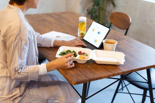 タブレットPCを見ながらテイクアウトフードで食事をするミドル女性