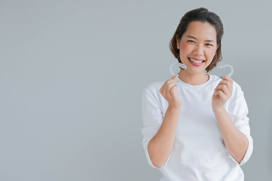 close up young asian woman smiling with hand holding dental aligner retainer (invisible) isolated on gray background of dental clinic for beautiful teeth treatment course concept