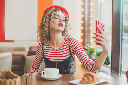 Young fashionable woman taking selfie in cafe