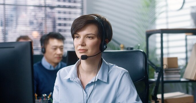 Close up portrait of happy young Caucasian beautiful female call center operator sitting at desk in cabinet in headset looking at camera and smiling. Joyful woman employee at work, worker concept