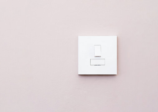 Light switch isolated on light purple wall, A plastic mechanical switch of white color installed on wall for turn on or turn off the lights inside of the room.