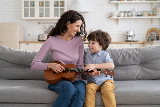 Young mother and little son sit together on couch at home and play ukulele guitar. Happy cheerful woman mom teach small boy music at coronavirus epidemic quarantine. Cute family spend time together