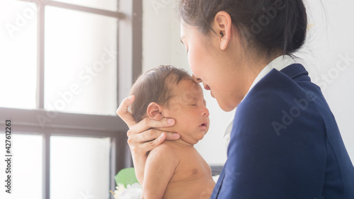 Young pretty mom kissing adorable little baby boy in the office. Single mother taking care of newborn child at the work place. Business, mom and baby, women's day, mother's day  concept.