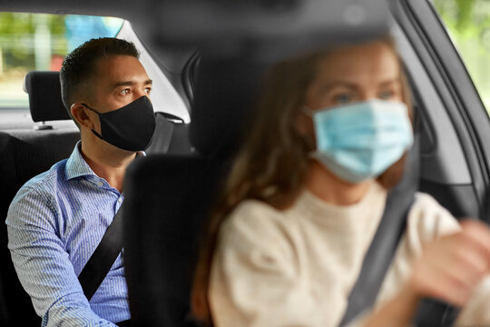 transportation, health and people concept - female driver driving car with male passenger wearing face protective medical mask for protection from virus disease