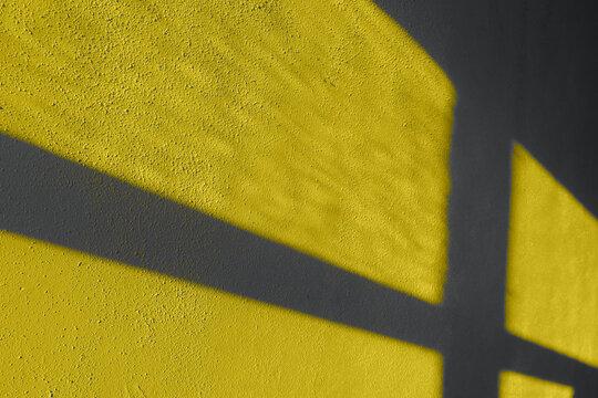 Textured wall shadows illuminating yellow and ultimate gray