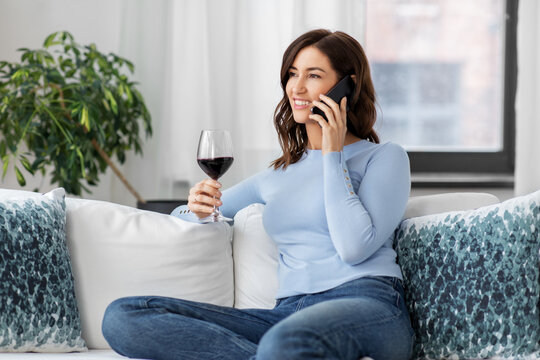 leisure and people concept - happy woman calling on smartphone and drinking red wine at home