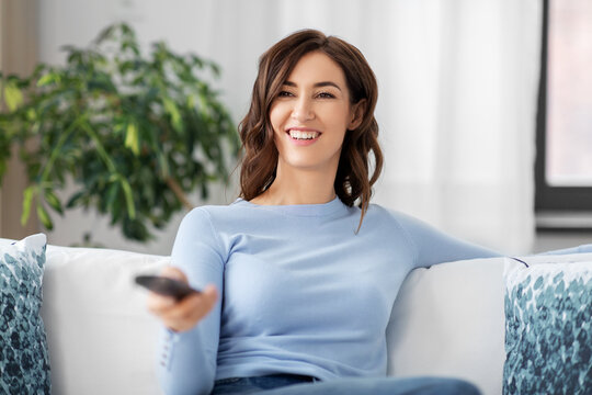 people and leisure concept - happy smiling young woman with remote control watching tv at home