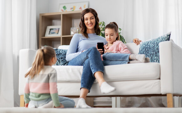 people, family and technology concept - happy mother and two daughters with smartphone at home