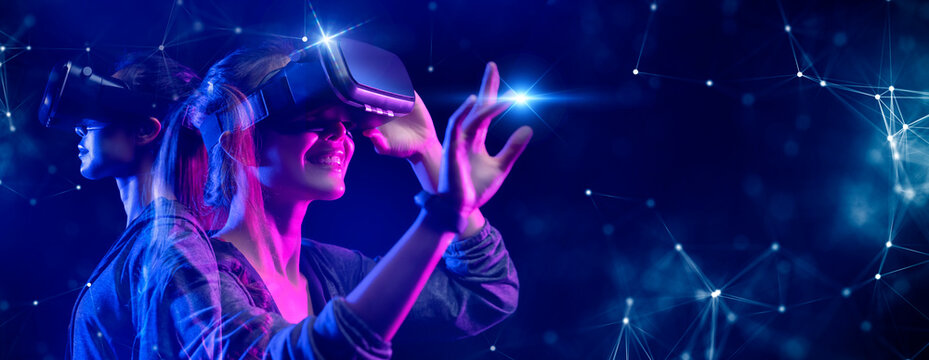 Teenager having fun play VR virtual reality glasses sport game 3D cyber space futuristic neon colorful background, future digital technology game and entertainment