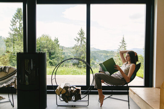 Beautiful stylish woman reading book, sitting on chair at fireplace on background of mountain hills
