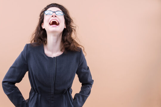 Young beautiful curly hair woman in glasses wearing casual jacket over beige background smiling and laughing hard out loud because funny crazy joke with hands on body. Business lady concept.